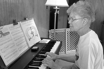 This is a photo of a woman learning to play the keyboard at A1 Music Studios.