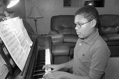 This photo is of a young student who is learning to play the piano.