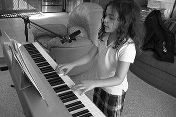 This is a photo of a five year old little girl learning to play the keyboard at A1 Studios.